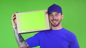 Szczęśliwego deliveryman kładzenia uśmiechnięty karton z copyspace na jego ramieniu zbiory wideo