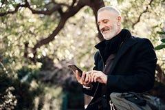 Szczęśliwego dorosłego atrakcyjnego biznesmena texting wiadomość na telefonie komórkowym podczas gdy siedzący w miasto parku przy Obrazy Royalty Free