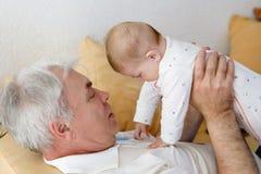 Szczęśliwego dziadek mienia dziewczynki uroczy wnuk na rękach obraz royalty free