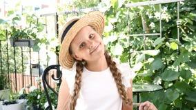 szczęśliwego dzieciństwa Portret śliczny małej dziewczynki obsiadanie w ulicznej kawiarni, ono uśmiecha się, trzymający jej swój  zdjęcie wideo