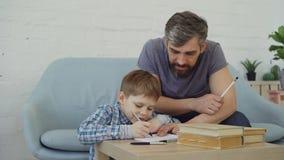 Szczęśliwego dziecka assiduous uczeń robi pracie domowej i opowiada jego ojciec, chłopiec uczy się i tata uczy zbiory