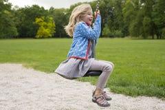 Szczęśliwego dziecka blond dziewczyna (wiek 5) ono pozbywa się na Latającego Fox sztuki wyposażeniu w children boisku fotografia royalty free