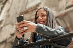 Szczęśliwego dziewczyny dopatrywania interneta ogólnospołeczni środki w telefonie komórkowym obraz royalty free