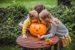 szczęśliwego halloween Ojca i dwa córek spojrzenia inside rzeźbiąca bania dla Halloweenowego outside zdjęcia stock
