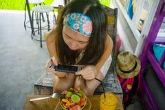 Szczęśliwego i dosyć cyfrowego koczownika Azjatycka Koreańska kobieta bierze obrazek owocowa sałatka z telefonem komórkowym dla d obraz stock