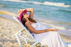 Szczęśliwego kobieta w ciąży odpoczynkowy lying on the beach na lounger morzem obrazy royalty free