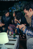 Szczęśliwego mężczyzna przyglądający smartphone w przyjęciu z przyjaciółmi zdjęcie stock