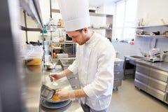 Szczęśliwego męskiego szefa kuchni kulinarny jedzenie przy restauracyjną kuchnią Fotografia Royalty Free