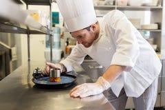 Szczęśliwego męskiego szefa kuchni kulinarny jedzenie przy restauracyjną kuchnią Obrazy Stock
