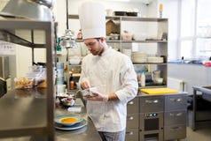 Szczęśliwego męskiego szefa kuchni kulinarny jedzenie przy restauracyjną kuchnią Zdjęcie Stock