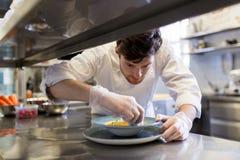 Szczęśliwego męskiego szefa kuchni kulinarny jedzenie przy restauracyjną kuchnią Zdjęcie Royalty Free