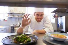 Szczęśliwego męskiego szefa kuchni kulinarny jedzenie przy restauracyjną kuchnią Obraz Royalty Free