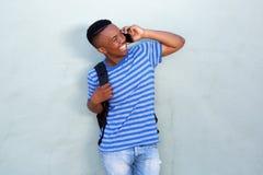 Szczęśliwego młodego amerykanina afrykańskiego pochodzenia męski uczeń opowiada na telefonie komórkowym Fotografia Royalty Free