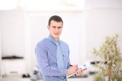 Szczęśliwego młodego biznesmena czytelnicza papierkowa robota w przy biurem Zdjęcia Royalty Free