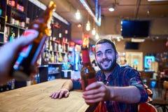 Szczęśliwego młodego człowieka Clinking butelki przy baru kontuarem Obraz Stock