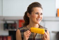 Szczęśliwego młodego gospodyni domowej łasowania gotowana kukurudza Zdjęcia Royalty Free