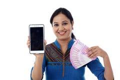Szczęśliwego młodej kobiety mienia Indiańska waluta i telefon komórkowy Obraz Stock