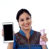 Szczęśliwego młodej kobiety mienia Indiańska waluta i telefon komórkowy Fotografia Royalty Free