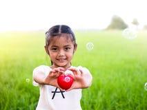 Szczęśliwego małego azjatykciego dziewczyny mienia czerwony serce i ono uśmiecha się Fotografia Stock