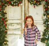Szczęśliwego małej dziewczynki mienia cukierku Bożenarodzeniowa trzcina fotografia royalty free
