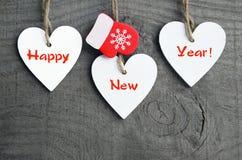 szczęśliwego nowego roku, Dekoracyjni biali drewniani Bożenarodzeniowi serca i czerwone mitynki na drewnianym tle Zima wakacji po Obraz Stock