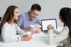 Szczęśliwego pary podpisywania kontraktacyjna bierze pożyczka przy spotkaniem z bankiem w zdjęcie royalty free