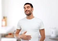 Szczęśliwego pełnego mężczyzna wzruszający brzuszek nad kuchnią obraz stock