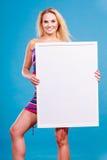 Szczęśliwego pozytywnego blondynki kobiety mienia pusta biała deska Zdjęcie Stock