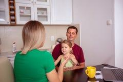 """Szczęśliwego rodzinnego †""""kobieta i mężczyzna bawić się z ich dziewczyną w domu fotografia stock"""