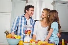 Szczęśliwego rodzinnego narządzania owocowy sok przy stołem Fotografia Royalty Free