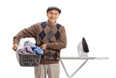 Szczęśliwego starszego mienia pralniany kosz przed prasowanie deską zdjęcia stock