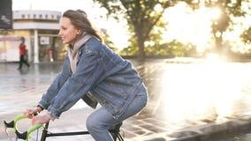 Szczęśliwego, uśmiechniętej kobiety rowerowy jeździec, przejażdżkę w ranku w miasto parku lub ulicie Obiektyw migocze na tle zbiory