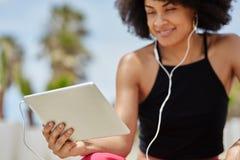 Szczęśliwej afro amerykańskiej kobiety słuchająca muzyka na pastylce Obrazy Stock
