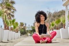 Szczęśliwej afro amerykańskiej kobiety słuchająca muzyka na pastylce na plaży Zdjęcie Stock