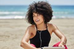 Szczęśliwej afro amerykańskiej kobiety słuchająca muzyka na plażowy patrzeć daleko od Obrazy Royalty Free