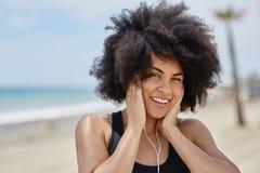 Szczęśliwej afro amerykańskiej kobiety słuchająca muzyka na plażowym mienia earph Zdjęcie Stock