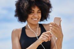 Szczęśliwej afro amerykańskiej kobiety słuchająca muzyka na wiszącej ozdobie Zdjęcie Stock