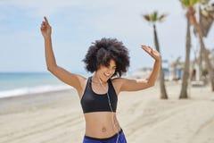 Szczęśliwej afro amerykańskiej kobiety słuchający muzyczny taniec na plaży Fotografia Stock