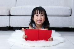 Szczęśliwej Azjatyckiej Chińskiej małej dziewczynki czytelnicza książka na podłoga Zdjęcie Royalty Free