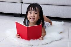 Szczęśliwej Azjatyckiej Chińskiej małej dziewczynki czytelnicza książka na podłoga Obrazy Stock