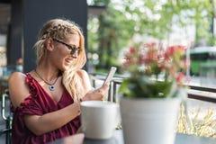 Szczęśliwej blondynki piękna kobieta używa telefon komórkowego pije filiżankę Obrazy Stock