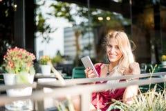 Szczęśliwej blondynki piękna kobieta używa telefon komórkowego pije filiżankę Zdjęcie Royalty Free