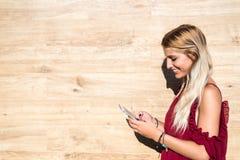 Szczęśliwej blondynki piękna kobieta używa telefon komórkowego pije filiżankę Zdjęcia Stock