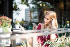 Szczęśliwej blondynki piękna kobieta używa telefon komórkowego pije filiżankę Obrazy Royalty Free