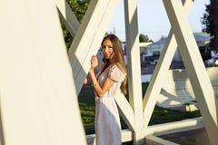 Szczęśliwej brunetki kobiety sukni relaksująca zabawa opiera na drewnianym stosu parku cieszy się twój wakacje, mody stylowy mias Fotografia Stock
