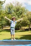 Szczęśliwej chłopiec skokowa wysokość na trampoline w parku obrazy stock