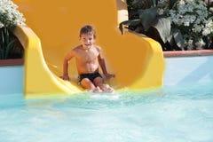 Szczęśliwej dziecka chłopiec jeździeccy obruszenia w aqua parku Zdjęcia Stock