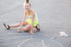 Szczęśliwej dziewczyny rysunkowa kreda na asfalcie zdjęcia stock
