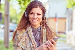 Szczęśliwej dziewczyny słuchająca muzyka z hełmofonami na smartphone w ulicie na jesień słonecznym dniu obrazy royalty free