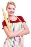Szczęśliwej gospodyni domowej kuchenny fartuch trzyma tocznej szpilki odizolowywa fotografia royalty free